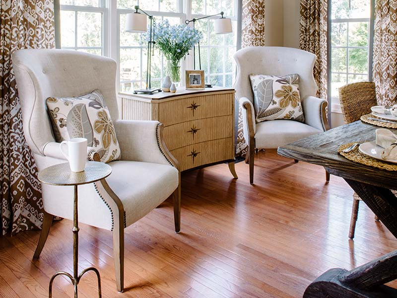 A pair of restoration hardware wing chairs abuts a sandblasted oak global views chest mixing high and low the table lamps are by visual comfort